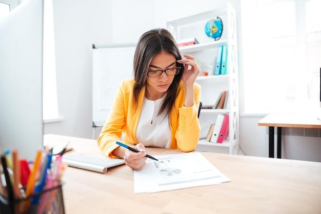 Mulher de negócios encantadora trabalhando com papel no escritório