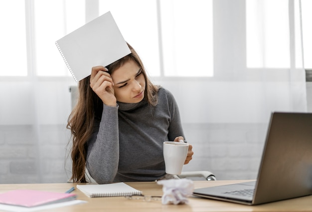 Mulher de negócios entediada segurando um bloco de notas em branco