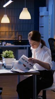 Mulher de negócios entra na sala de reuniões do escritório da empresa tarde da noite, sentada na mesa à noite
