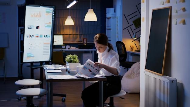 Mulher de negócios entra na sala de reuniões do escritório da empresa tarde da noite, sentada na mesa até tarde da noite, trabalhando no lucro de marketing, analisando estatísticas