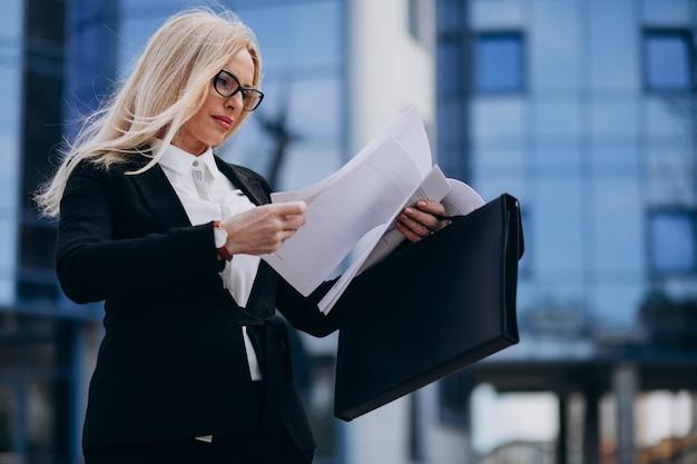 Mulher de negócios envelhecida média segurando documentos pelo centro de negócios