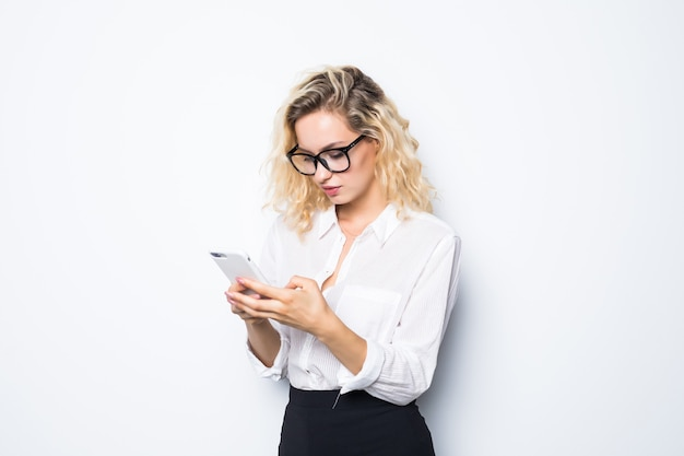 Mulher de negócios enviando mensagens de texto em seu celular isolado na parede branca