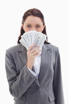 Mulher de negócios escondida atrás de muitos dólares de notas de banco