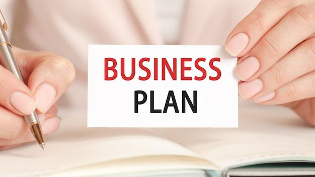 Mulher de negócios escreve em um caderno com uma caneta prateada e um cartão de mão