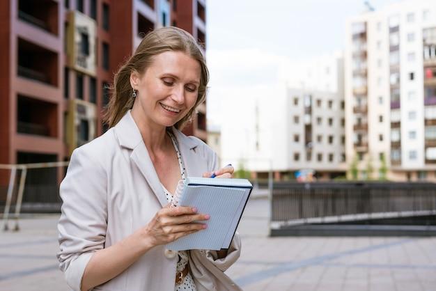 Mulher de negócios, escrevendo com a caneta no caderno caucasiana, garota bem sucedida com jaqueta leve fica perto de um ...
