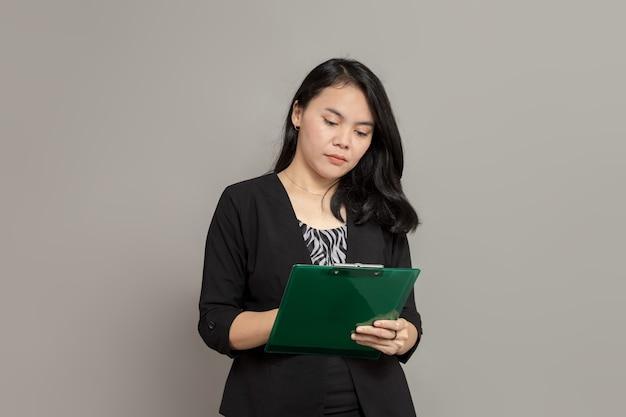 Mulher de negócios escrevendo na prancheta com expressão facial plana