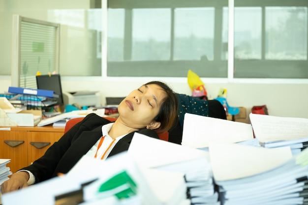Mulher de negócios esgotada que dorme na mesa no escritório com a pilha do paperwok.