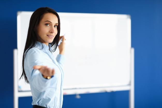 Mulher de negócios está de pé no escritório e está escrevendo no quadro branco