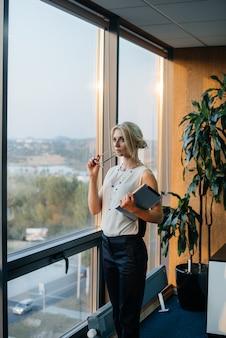 Mulher de negócios está de pé no escritório perto da janela e está estudando documentos. negócios, finanças, advogado