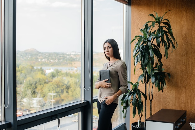 Mulher de negócios está de pé no escritório perto da janela e está estudando documentos.