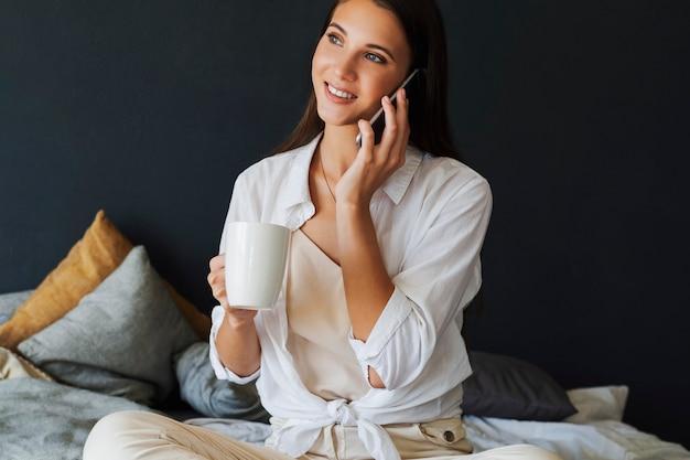 Mulher de negócios está falando ao telefone, negociando, marcando um encontro com amigos. menina sorridente em uma camisa branca se senta na cama, ao lado do laptop. menina morena no quarto.