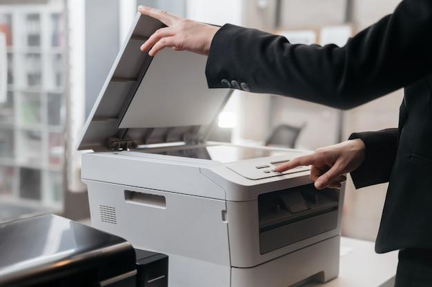 Mulher de negócios está usando a impressora para digitalizar e imprimir documentos