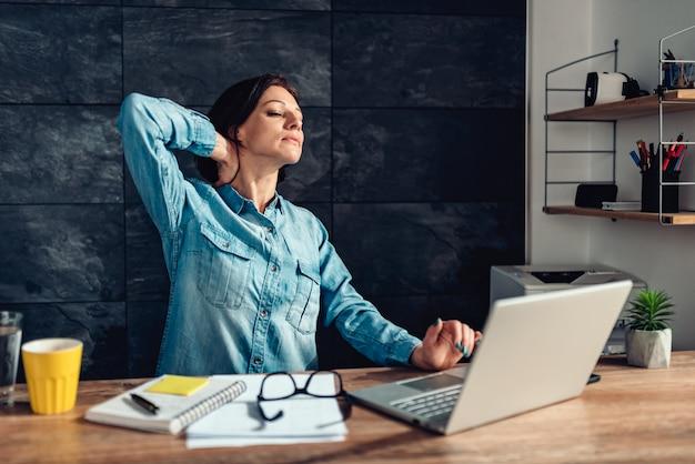 Mulher de negócios, esticando os braços no escritório