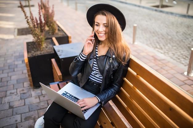 Mulher de negócios estudante garota sentada em um banco de madeira na cidade no parque no outono