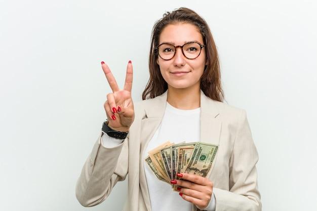 Mulher de negócios europeia jovem segurando as notas de dólar, mostrando o número dois com os dedos.