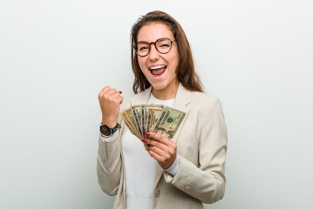 Mulher de negócios europeia jovem segurando notas de dólar torcendo despreocupado e animado.