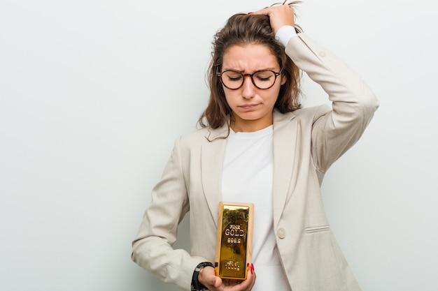 Mulher de negócios europeu jovem segurando um lingote de ouro sendo chocado, ela se lembrou de uma reunião importante.