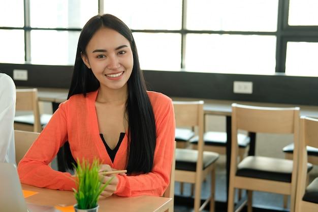 Mulher de negócios executivo asiático sorrindo no local de trabalho de negócios