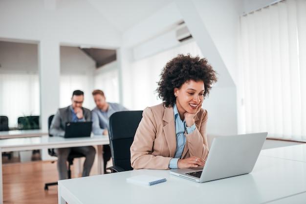 Mulher de negócios exótica positiva que trabalha no portátil no escritório compartilhado.