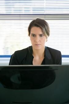 Mulher de negócios experiente sentada na sala do escritório e olhando para a tela. empregado de escritório bonito conteúdo caucasiano trabalhando no projeto através do computador. conceito de negócios, tecnologia digital e corporação