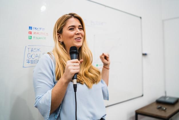 Mulher de negócios, explicando o plano de trabalho em conferência