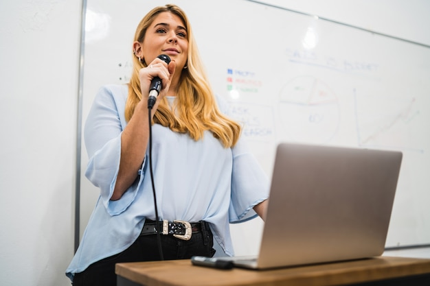 Mulher de negócios, explicando o plano de trabalho em conferência.