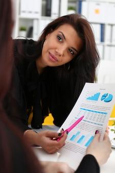 Mulher de negócios explicando quadro financeiro para colega