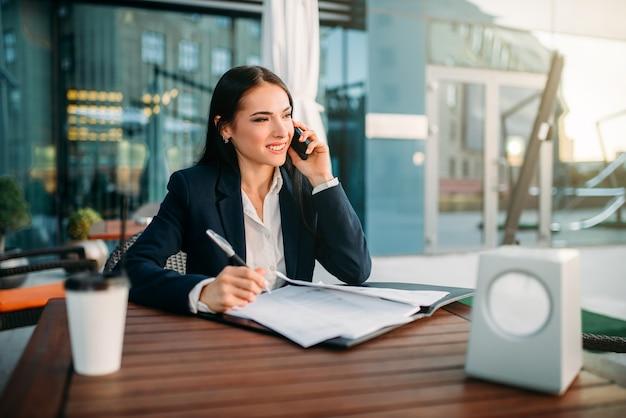 Mulher de negócios fala pelo celular no café. edifício moderno, centro financeiro, paisagem urbana. mulher de negócios de terno