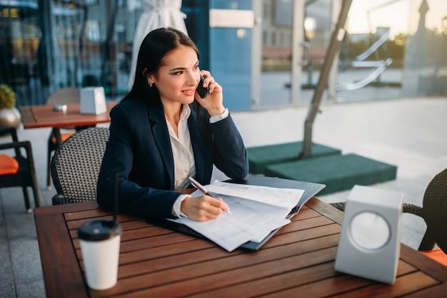 Mulher de negócios falando ao celular em um café