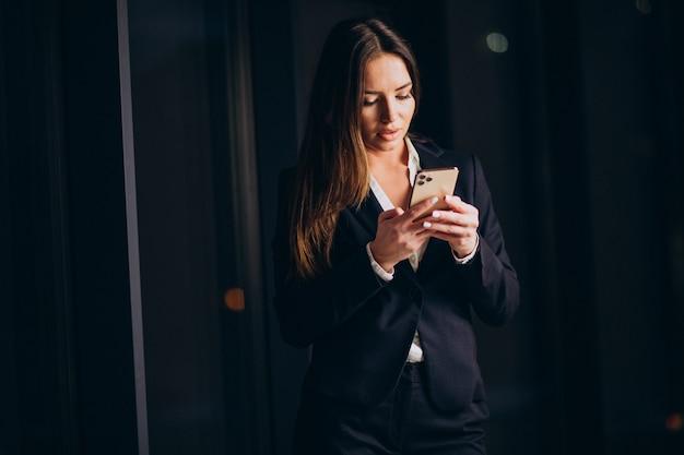 Mulher de negócios falando ao telefone e ficando até tarde da noite no escritório