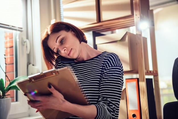 Mulher de negócios, falando ao telefone no escritório e escrevendo notas