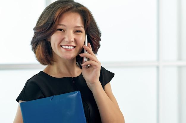 Mulher de negócios, falando ao telefone. retrato de menina bonita no escritório