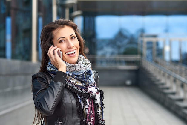 Mulher de negócios, falando ao telefone. retrato de uma menina bonita em azul urbano