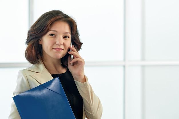 Mulher de negócios, falando ao telefone. retrato de uma menina bonita no escritório na janela branca