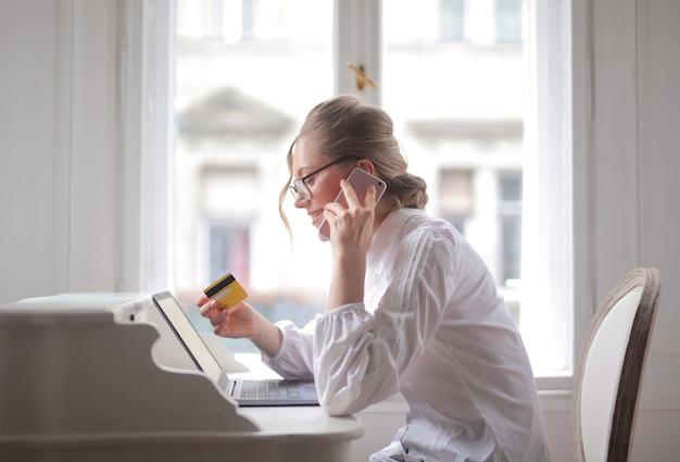 Mulher de negócios falando ao telefone, segurando um cartão de crédito e sorrindo