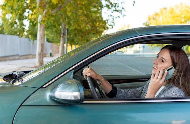 Mulher de negócios falando com seu telefone e pronta para dirigir seu carro depois de sair do escritório.