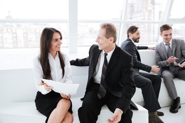 Mulher de negócios falando com um parceiro de negócios e sentada no sofá no escritório com colegas