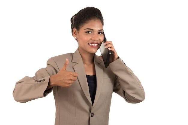 Mulher de negócios, falando no celular e aparecendo o polegar isolado no fundo branco.