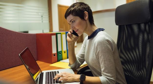 Mulher de negócios falando no celular enquanto usa o laptop no escritório