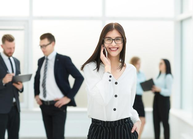 Mulher de negócios, falando no celular no saguão do escritório. foto com espaço de cópia