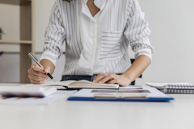 Mulher de negócios faz anotações em um caderno, verifica documentos de vendas e financeiros em seu escritório particular, é executiva de uma startup. conceito de administração de empresas.