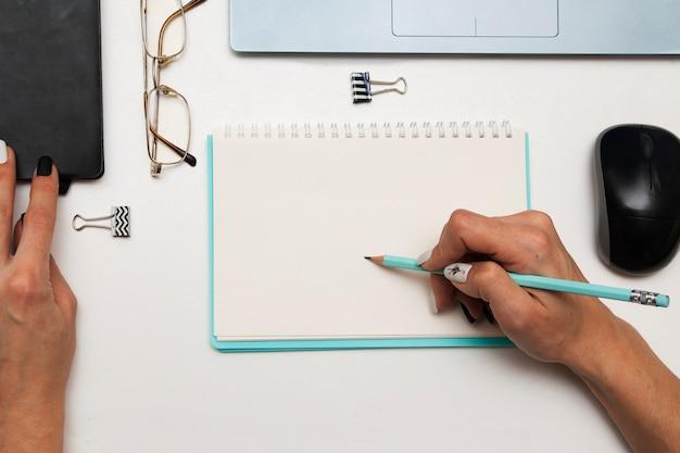 Mulher de negócios faz uma entrada em um caderno em cima da mesa
