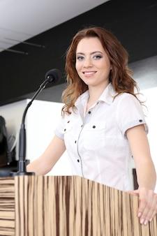 Mulher de negócios fazendo discurso na sala de conferências