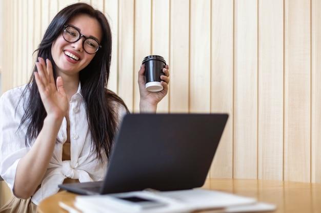 Mulher de negócios feliz acenando com a mão falando de videochamada online usar laptop sentado à mesa no café