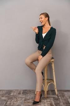 Mulher de negócios feliz alegre em pé isolado sobre o apontador de fundo de parede cinza.