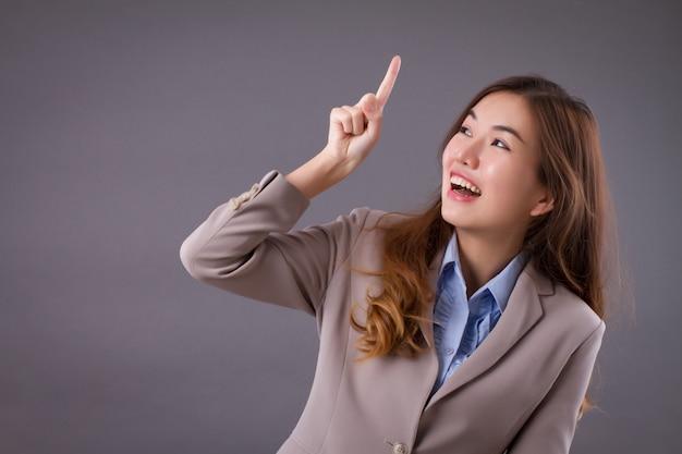 Mulher de negócios feliz apontando para cima