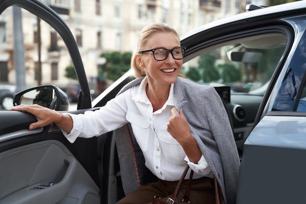Mulher de negócios feliz atraente em roupa clássica saindo de seu carro moderno e sorrindo