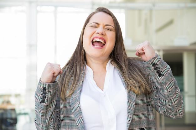 Mulher de negócios feliz bombeamento punhos ao ar livre