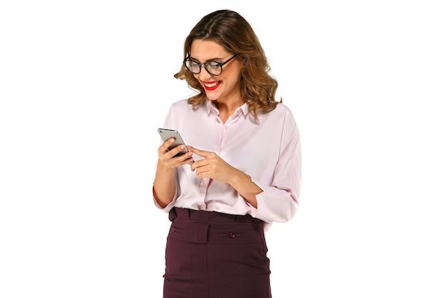 Mulher de negócios feliz, bonita usando telefone, folheando, vestida com roupas estritas