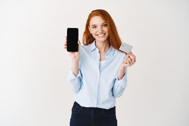 Mulher de negócios feliz com cabelo ruivo mostrando cartão de crédito de plástico e tela do smartphone em branco, demonstração do aplicativo de compras, parede branca